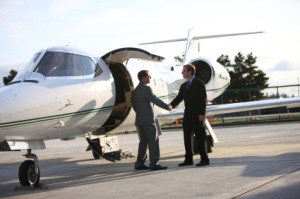 Businessmen shake hands by corporate jet